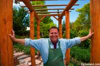 A middle aged man with arms outstretched between wooden poles with lots of greenery in the background. The man is a self-made small business owner and a successful one at that.